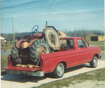 normal pickup truck wiht tractor loaded into the bed