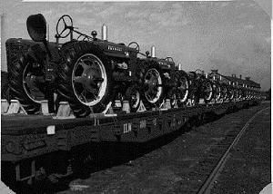 50s picture of brand new farmall tractors loaded on flat bed train cars