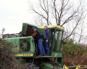 two men working on combine