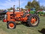 tractor is orange with rounded grill, black badge, narrow front