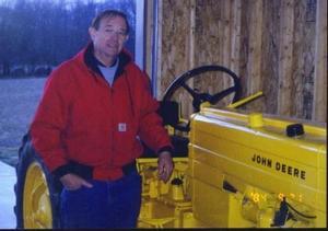 Jim McFarlane standing next to JD tractor